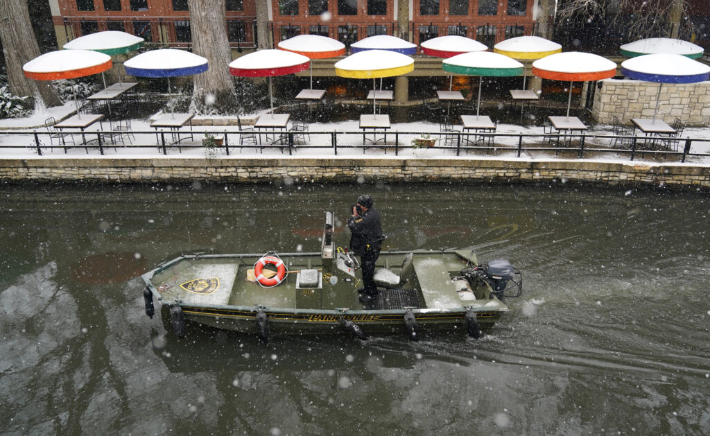 A Park Policeman patrols along the River Walk as snow falls, Thursday, Feb. 18, 2021, in San Antonio. Snow, ice and sub-freezing weather continue to wreak havoc on the state's power grid and utilities. (AP Photo/Eric Gay)