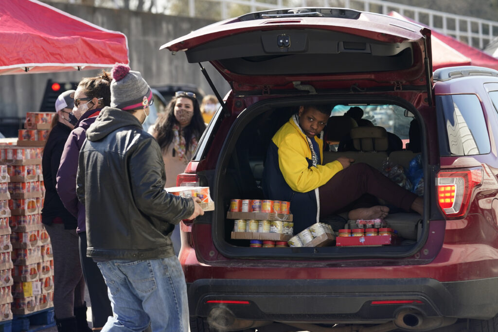 Volunteers hand out food and water at a San Antonio Food Bank drive-through food distribution site held at Rackspace Technology, Friday, Feb. 19, 2021, in San Antonio. (AP Photo/Eric Gay)
