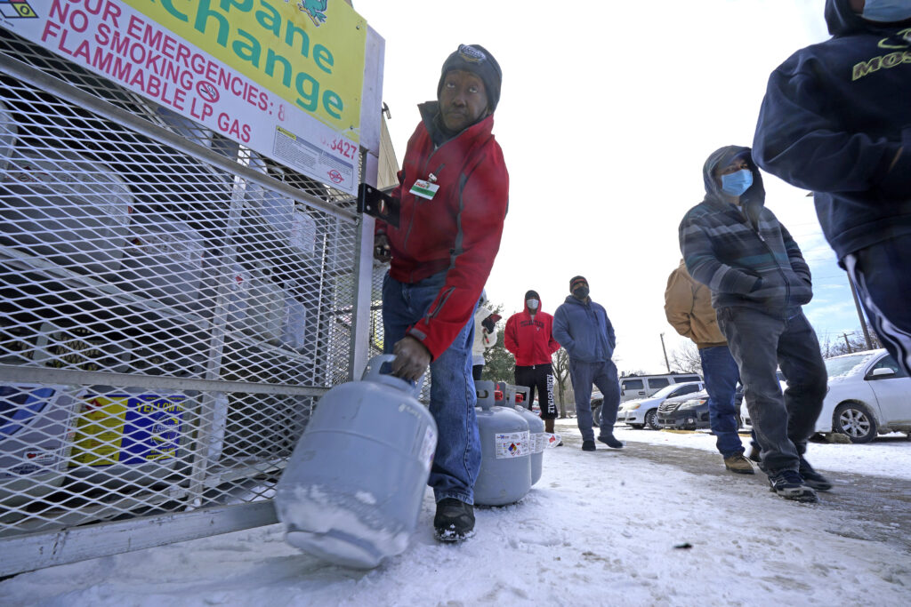 FILE - In this Feb. 16, 2021, file photo, Robert Webster pulls a full canister of propane for sale as customers line up to enter a grocery store in Dallas. As temperatures plunged and snow and ice whipped the state, much of Texas' power grid collapsed, followed by its water systems. Tens of millions huddled in frigid homes that slowly grew colder or fled for safety. (AP Photo/LM Otero, File)
