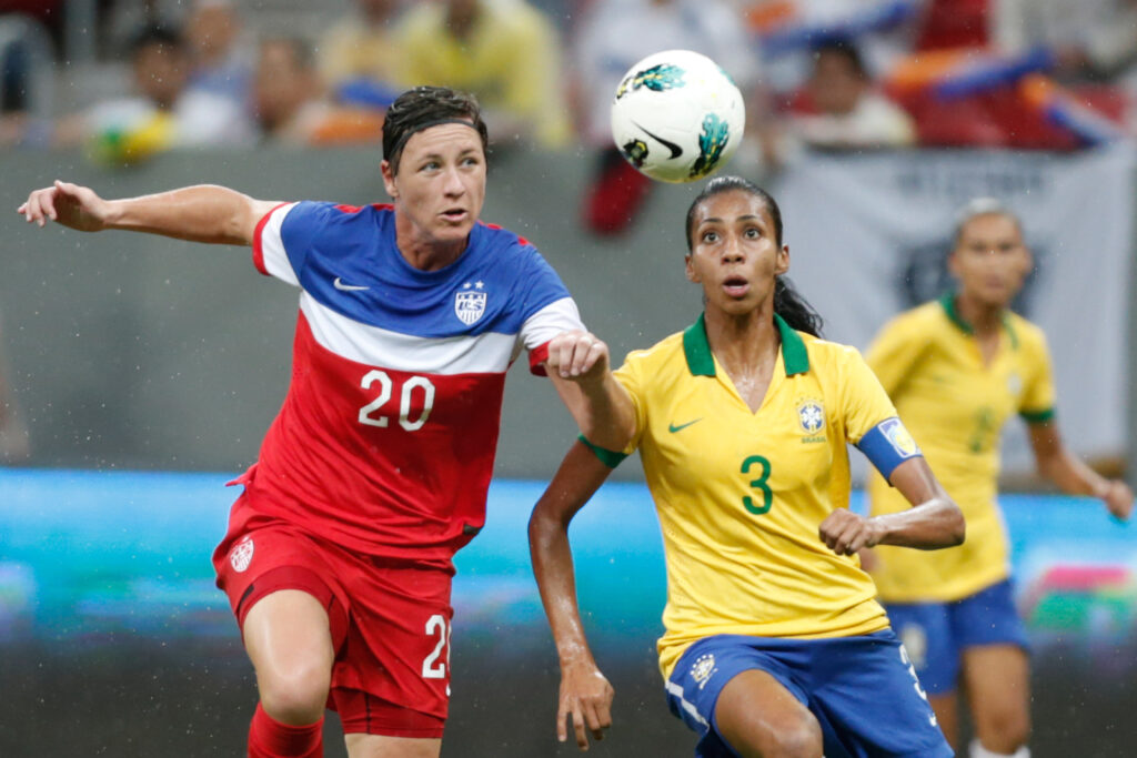 United States' Abby Wambach, left, fights for the ball with Brazil's Bruna Benites, right, during a final match of the International Women's Football Tournament at the National Stadium in Brasilia, Brazil, Dec. 21, 2014.