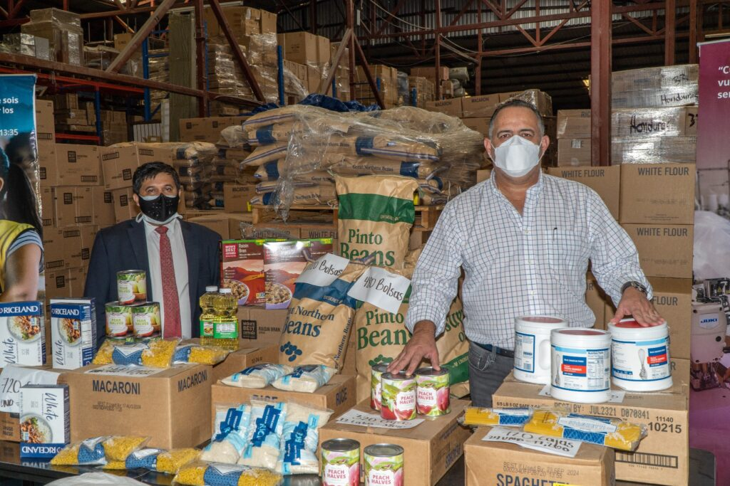 Elder José Bernardo Hernández, an Area Seventy, left, and San Pedro Mayor Armando Calidonio Alvarado are surrounded by over 171,000 pound of found donated by the Church to assist hurricane victims in the region.