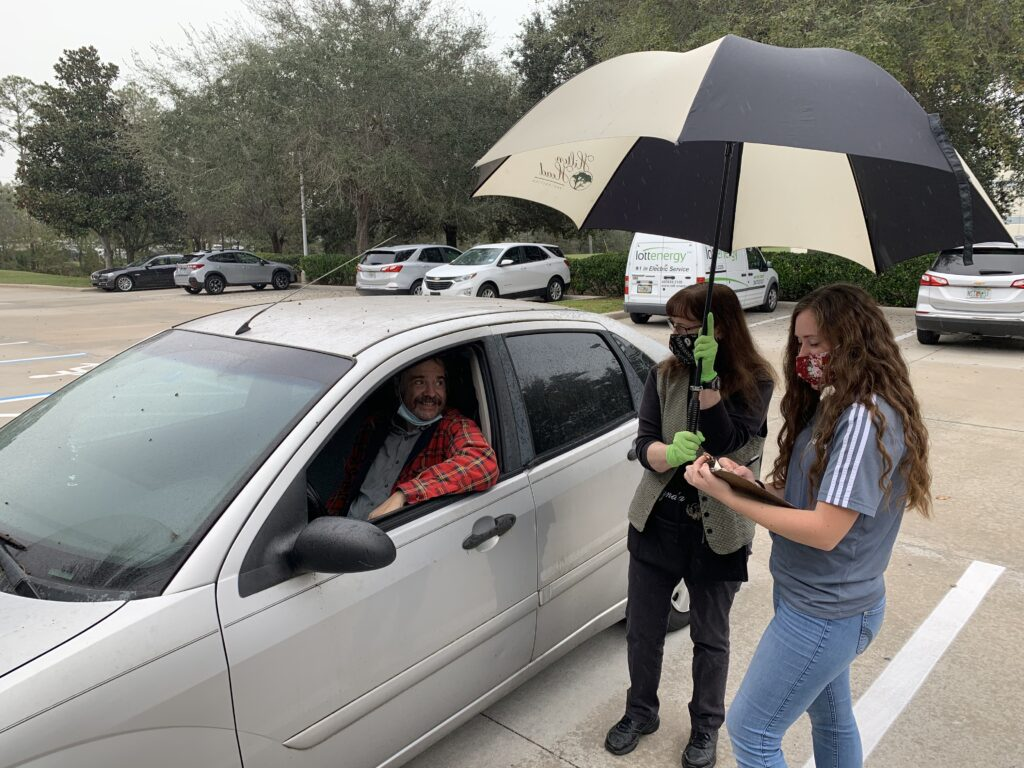 Sister Cadance Sanders, right, and Sister Cynda Aron greet a friend outside the Orlando Bishops' Storehouse. Missionaries from the Florida Orlando Mission have helped keep the storehouse in operation during the pandemic.
