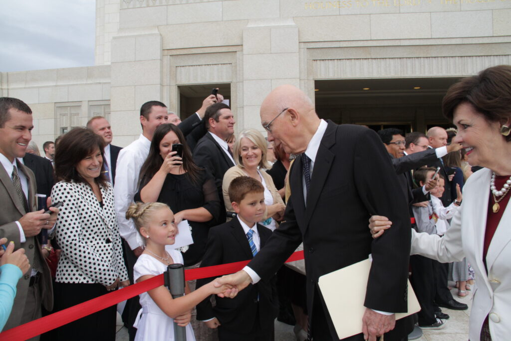 Elder Dallin H. Oaks of the Quorum of the Twelve shakes hands with cousins, Tayli Petersen, 9, and Payton Manning, 8, as he and Sister Kristen Oaks leave the Ogden Utah Temple after its rededication on Sept. 21.