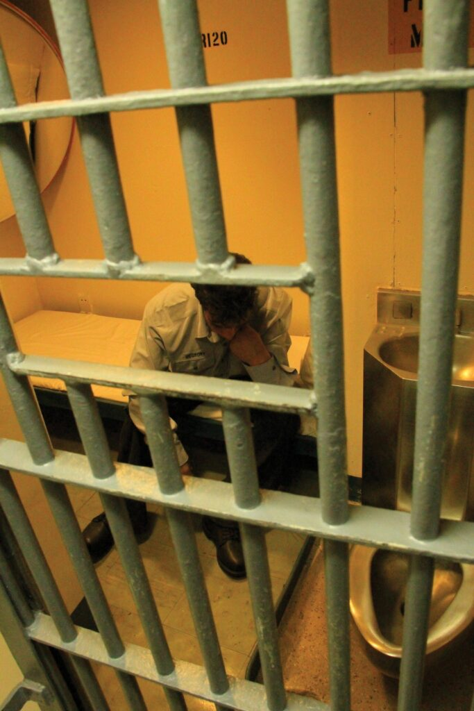 A man sits in a prison cell.