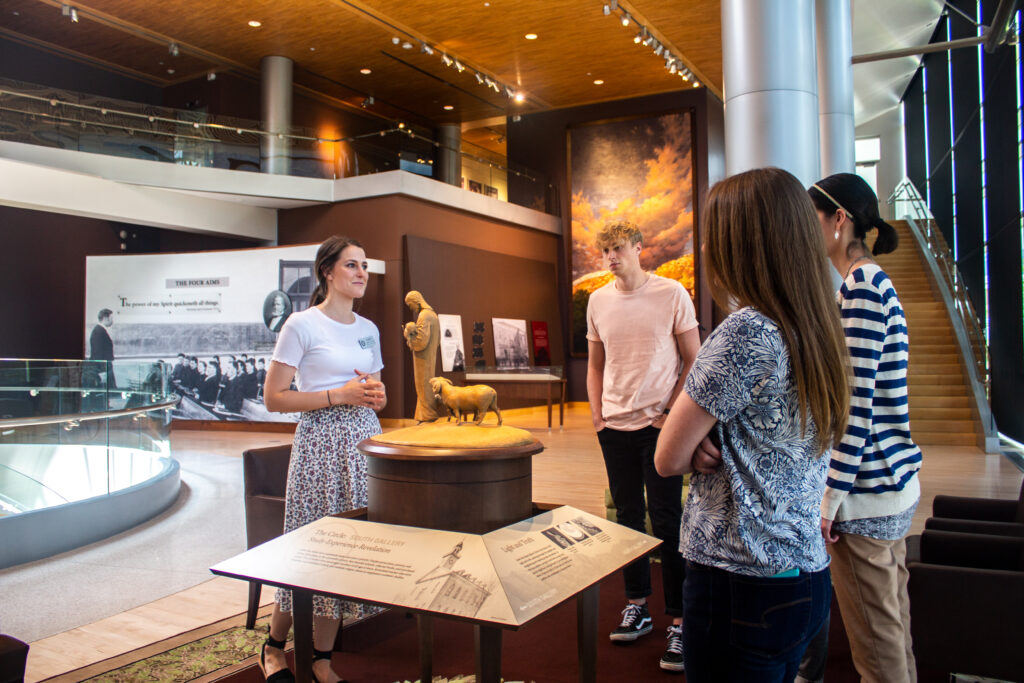 Prior to the pandemic, a guide welcomes visitors to BYU's Education in Zion Gallery.