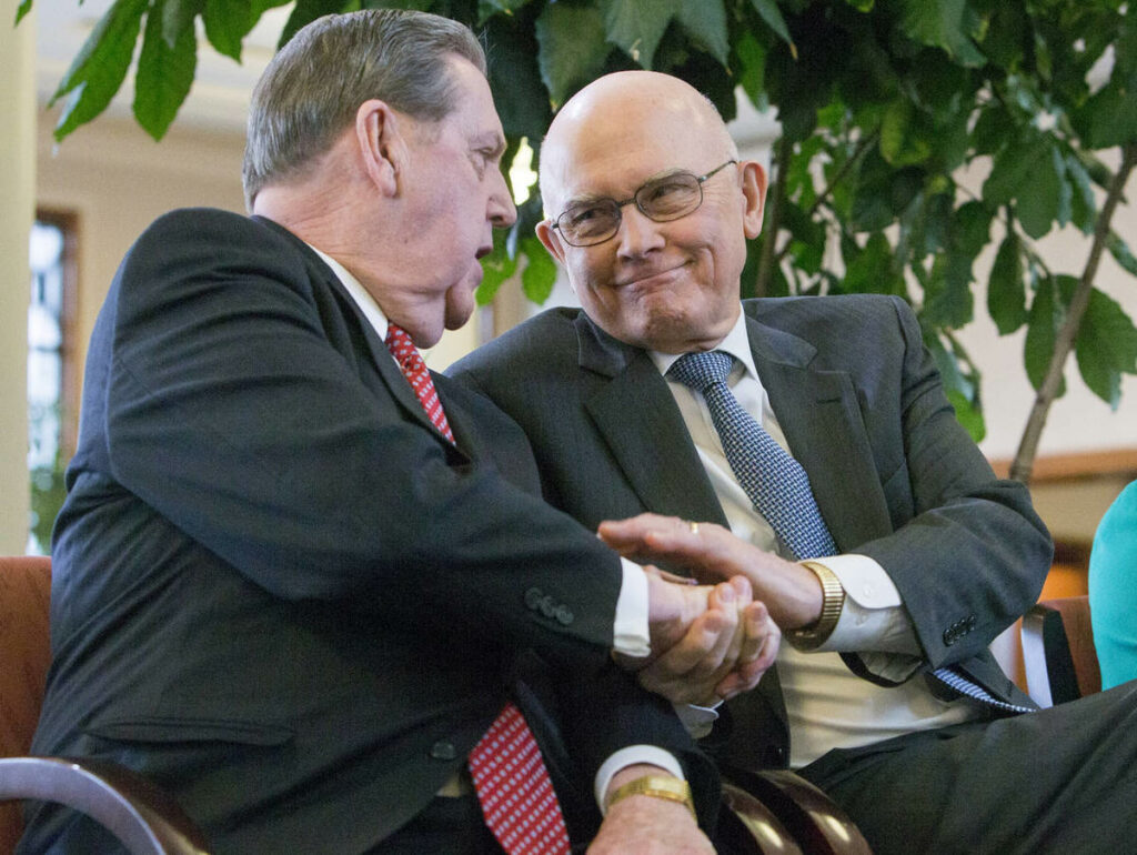 Elder Jeffrey R. Holland, of the Quorum of the Twelve Apostles of The Church of Jesus Christ of Latter-day Saints, and Elder Dallin H. Oaks, of the Quorum of the Twelve Apostles, shake hands inside the Conference Center in Salt Lake City after a news conference on Tuesday, Jan. 27, 2015, where church leaders reemphasized support for LGBT nondiscrimination laws that protect religious freedoms.