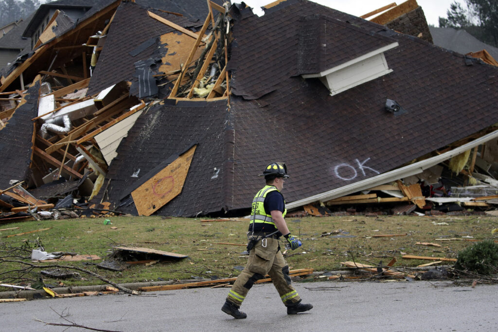 A firefighter surveys damage to a house after a tornado touches down south of Birmingham, Alabama, in the Eagle Point community damaging multiple homes Thursday, March 25, 2021. The National Weather Service issued multiple tornado warnings for Alabama and surrounding states.
