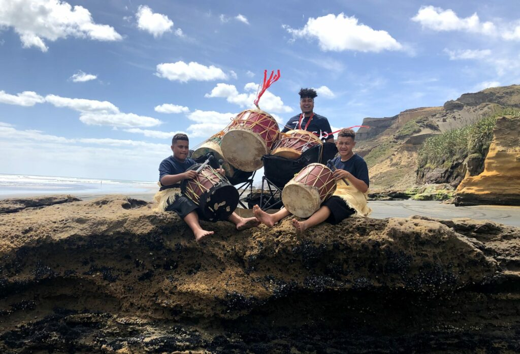 """Youth in New Zealand play during a performance of """"He is Risen"""" during the Youth Music Festival on March 17, 2021. This performance was filmed on a beach near Auckland."""