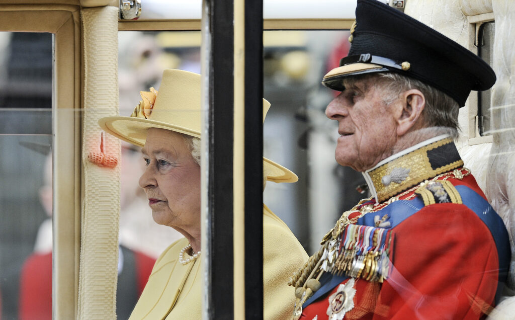 In this April 29, 2011, file photo, Britain's Prince Phillip sits beside Queen Elizabeth II in a carriage leaving Westminster Abbey after the royal wedding of Prince William and Kate Middleton in London. Prince Philip, the irascible and tough-minded husband of Queen Elizabeth II who spent more than seven decades supporting his wife in a role that both defined and constricted his life, has died, Buckingham Palace said Friday. He was 99.