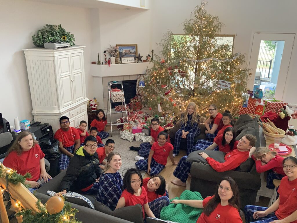 The McKendrick family is pictured together in their Gilbert, Arizona, living room during Christmas 2020. This photo includes 18 of the 24 McKendrick children and one daughter-in-law.
