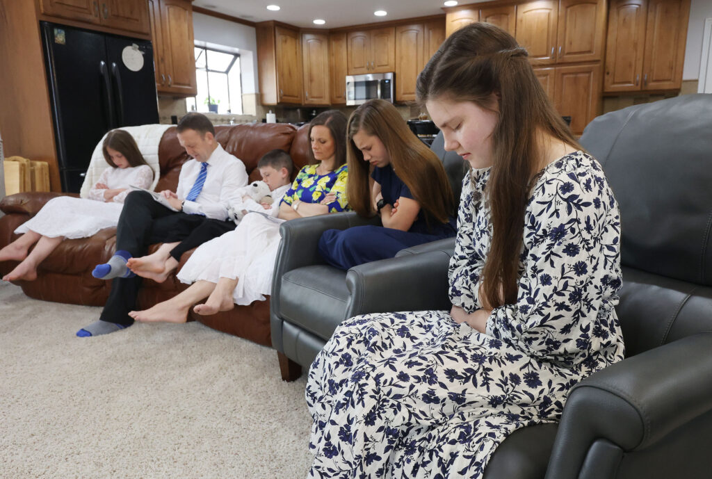 Margaret Ann Ballard listens to the prayer with parents Chris and Melanie Ballard as they watch the 191st Annual General Conference of The Church of Jesus Christ of Latter-day Saints at their home in Taylorsville on Sunday, April 4, 2021.