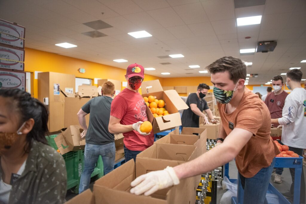 Missionaries in the California San Jose Mission of The Church of Jesus Christ of Latter-day Saints help box food at Second Harvest of Silicon Valley in February 2021. Elders and Sisters worked to distribute food to more than 500,000 people each month during the COVID-caused statewide lockdown. In ten months, missionaries have donated more than 13,000 hours at Second Harvest to help fill those needs.