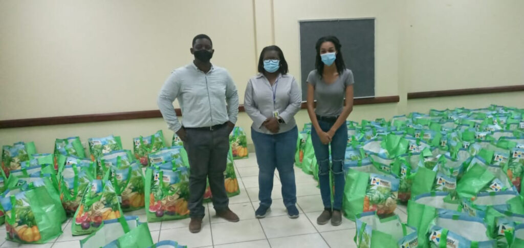 Kingstown Branch President Rayshorn Richardson, left, Michelle Forbes, director of Saint Vincent and the Grenadines National Emergency Management Organization, center, Ronique Forbes, the church's communication director in St. Vincent, right, stand among the 200 food hampers donated by the Church to the National Emergency Management Organization to distribute among people in shelters in face of the La Soufrière volcano eruptions and explosions on St. Vincent in April 2021.