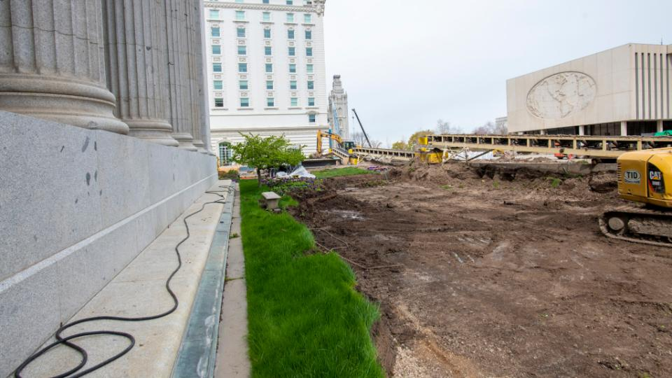 Looking west on the Church Office Building plaza, shows the Church Administration Building, left, the Joseph Smith Memorial Building, center, and Church Office Building, right, in May 2021. Crews are using conveyor belts to move soil and debris to a truck loading location.