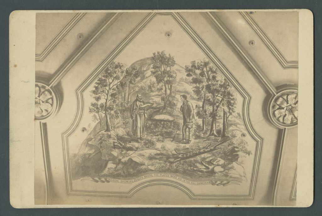 """""""Moroni showing Joseph where the plates were hid in the Hill Cumorah"""" mural on the Assembly Hall ceiling was painted in 1880 by W.C. Morris. On the reverse of this photograph, taken by C. W. Carter, is this description: """"The interior dimensions are 116x64 feet, the ceiling 40 feet from the floor; is divided off into 16 historical painted panels, by W.C. Morris, the largest of which is 30 feet at the base, opening triangularly towards the center, representing the angel Moroni showing to Joseph where the plates were hid on the hill Cumorah. The panes above the three stands, and in front of the organ, contain the All seeing Eye. The hive of Deseret being flanked by the Nauvoo and Kirtland Temples. The next panel east on the north side depicts Joseph receiving the Melchizedek Priesthood from Peter, James and John; and first on the south side Joseph and Oliver receiving the Aaronic Priesthood from John the Baptist. Over the north side entrance is the date of arrival of the Pioneers in Salt Lake City. The panels above this contain the Salt Lake and Logan Temples. Similarly placed on the south side is date of organization of the Church and St. George and Manti Temples. The panels above represent the Savior, Moses, Elijah and Elias."""""""