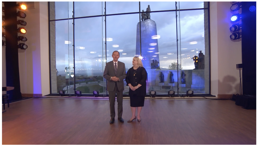 Elder and Sister Stevenson stand in front of the vaulted windows of the Pioneer Center overlooking the This Is The Place Monument and the Salt Lake Valley.