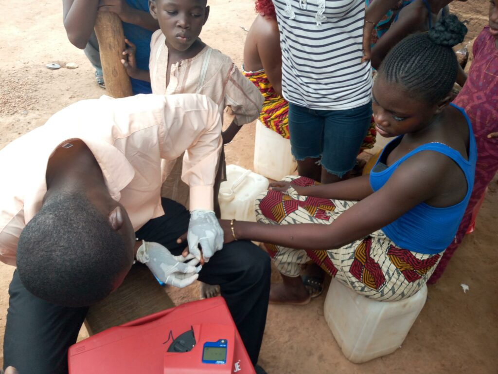 A technician in Senegal tests a young woman's blood to screen for iron deficiency anemia. The Church and its humanitarian partners sponsor an ongoing nutrition program to battle anemia in Senegal and Benin.
