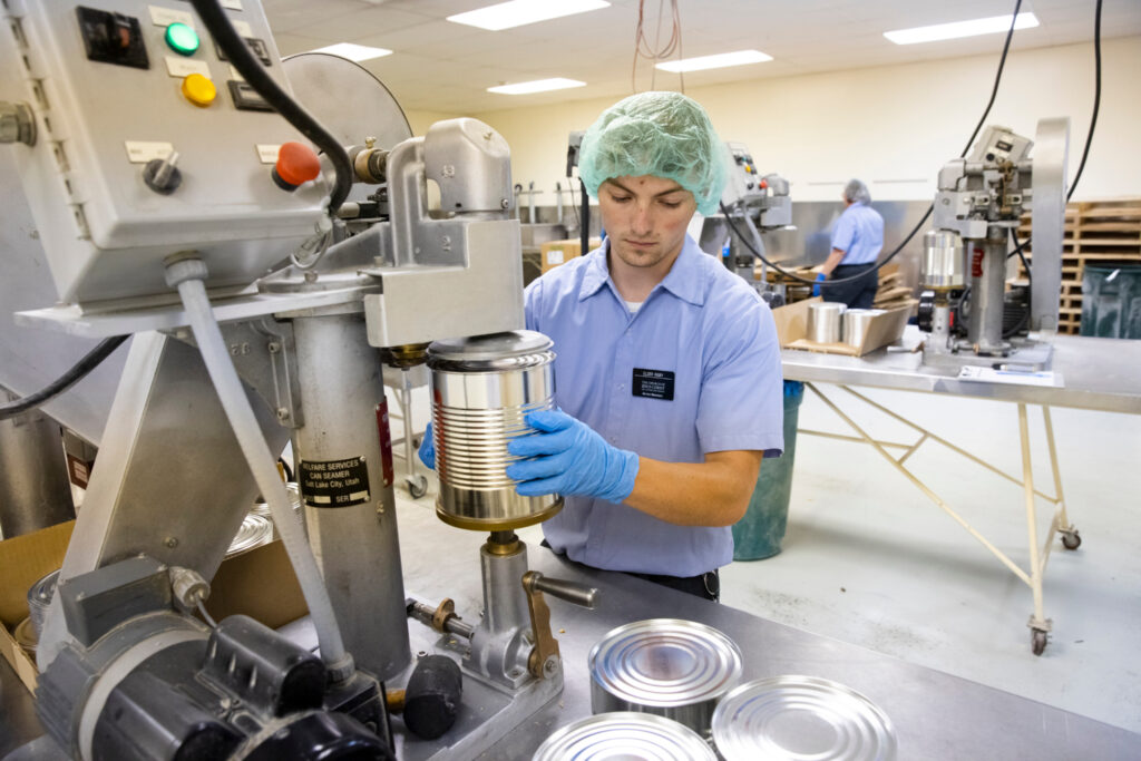 Elder Caleb Rigby, a missionary, seals No. 10 cans full of dried apples at the Church-owned Deseret Mill and Pasta Plant in Kaysville, Utah, on Wednesday, May 26, 2021.