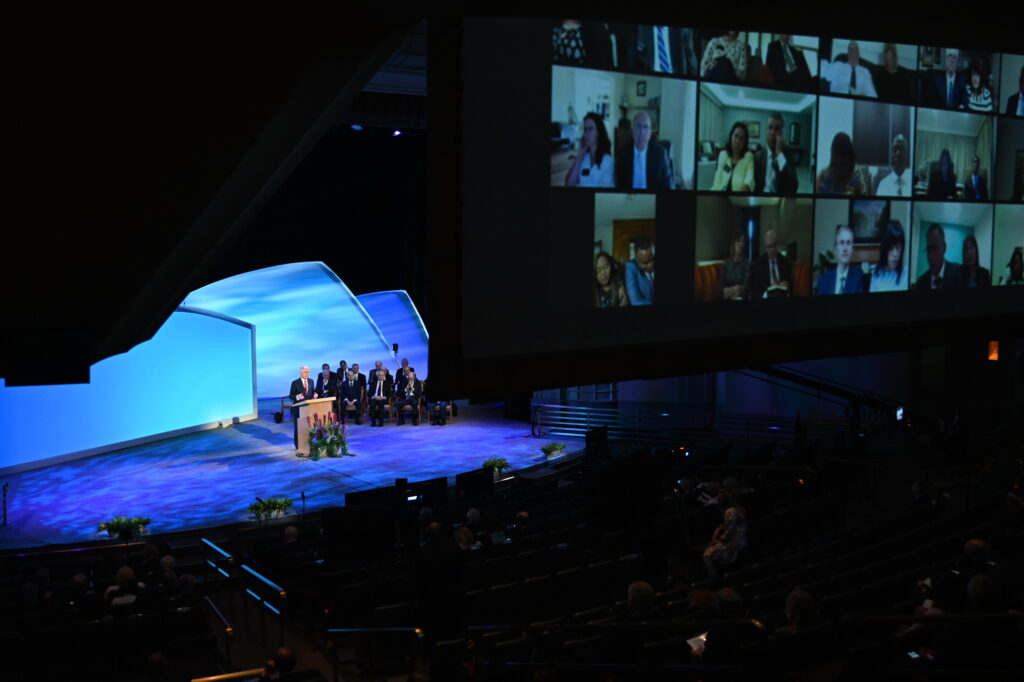 With screens showing views of the participating new mission presidents and companions, Elder Dieter F. Uchtdorf of the Quorum of the Twelve Apostles speaks during the Thursday, June 24, session of the 2021 Seminar for New Mission Leaders, held in the Conference Center Theater.