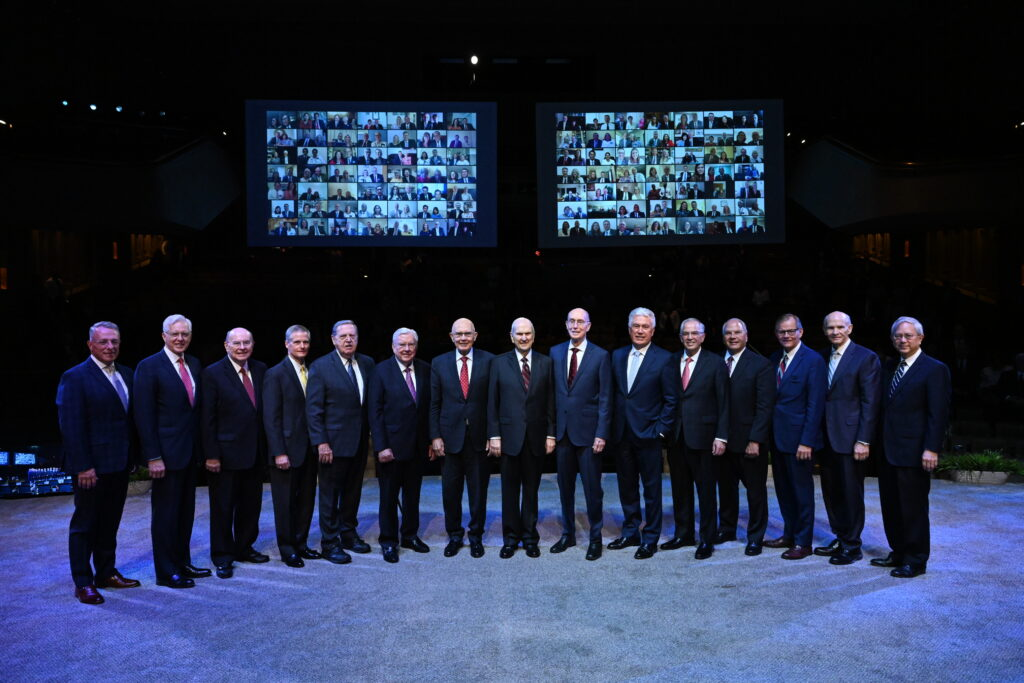 In front of a backdrop of screens showing the new mission presidents and companions participating remotely at home, the First Presidency and Quorum of the Twelve Apostles pause for a photo together before the start of the second day of the 2021 Seminar for New Mission Leaders on Friday, June 25, 2021, in the Conference Center Theater.