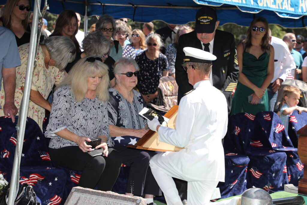 U.S. Navy Capt. Brian Anderson presents the flag of 48 stars in a memorial case to Karen Little during the military burial of her brother, Carl, who was killed at Pearl Harbor 80 years ago. The 48-star flag was the national flag in 1941. The services were June 26, 2021.