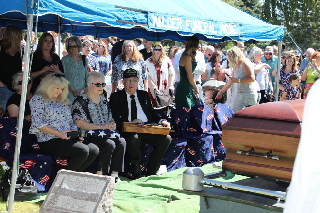 Karen Bradley Little, holding the folded flag, sits with by her husband, John Little, a veteran submariner, moments before members of the local American Legion offered the traditional 21-gun salute and the playing of the honorary bugle signal taps during the military burial in Shelley, Idaho, of Navy Fireman 2nd Class Carl M. Bradley. The services were June 26, 2021.