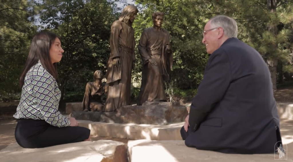 Elder Neil L. Andersen of the Quorum of the Twelve Apostles speaks with Marcela Rojas, left, in front of a bronze sculpture depicting the woman who touched the Savior's clothing and was healed. This video segment was shown during a Face to Face for young adults on Sunday, June 13, 2021.