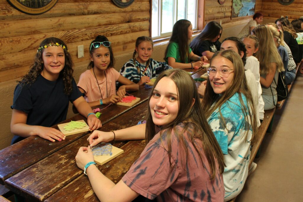 Young women from the Queen Creek Arizona South Stake make thread hearts on wood squares in a crafts rotation during a Young Women camp held at Camp LoMia near Pine, Arizona, on June 3, 2021.