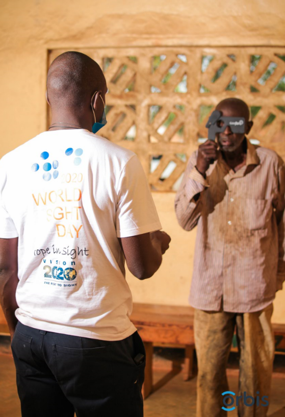A volunteer with Orbis, a partner of Latter-day Saint Charities, performs an eye screening on a man in Zambia in October 2020.