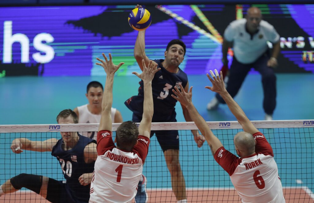 United States' Taylor Sander spikes the ball past Poland's Piotr Nowakowski and Bartosz Kurek during the Men's World Championships volleyball semifinal match between the United States and Poland, in Turin, Italy, Saturday, Sept. 29, 2018.