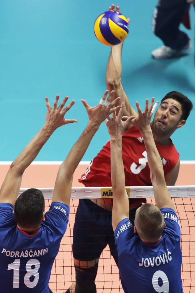 United States' Taylor Sander smashes as Serbia's Marko Podrascanin, left, and Serbia's Nikola Jovovic, jump to block during the Men's World Championships volleyball third-place match between USA and Serbia, in Turin, Italy, Sunday, Sept. 30, 2018.
