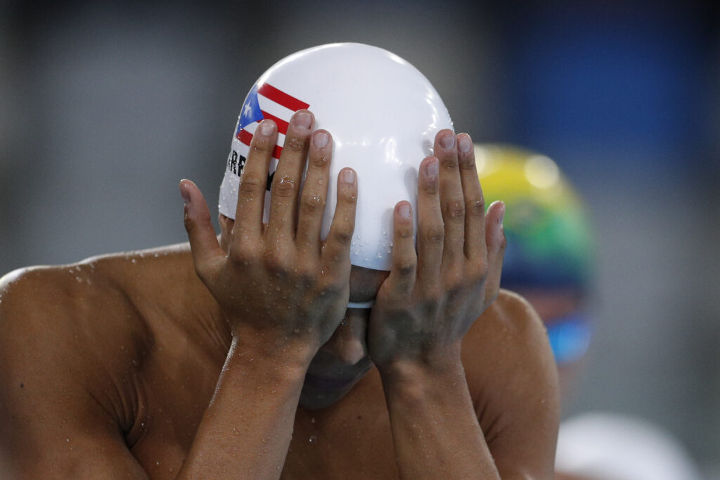 Puerto Rico's Jarod Arroyo adjusts his cap and goggles as he prepares to compete in a heat of the men's swimming 400m individual medley at the Pan American Games in Lima, Peru, Friday, Aug. 9, 2019.