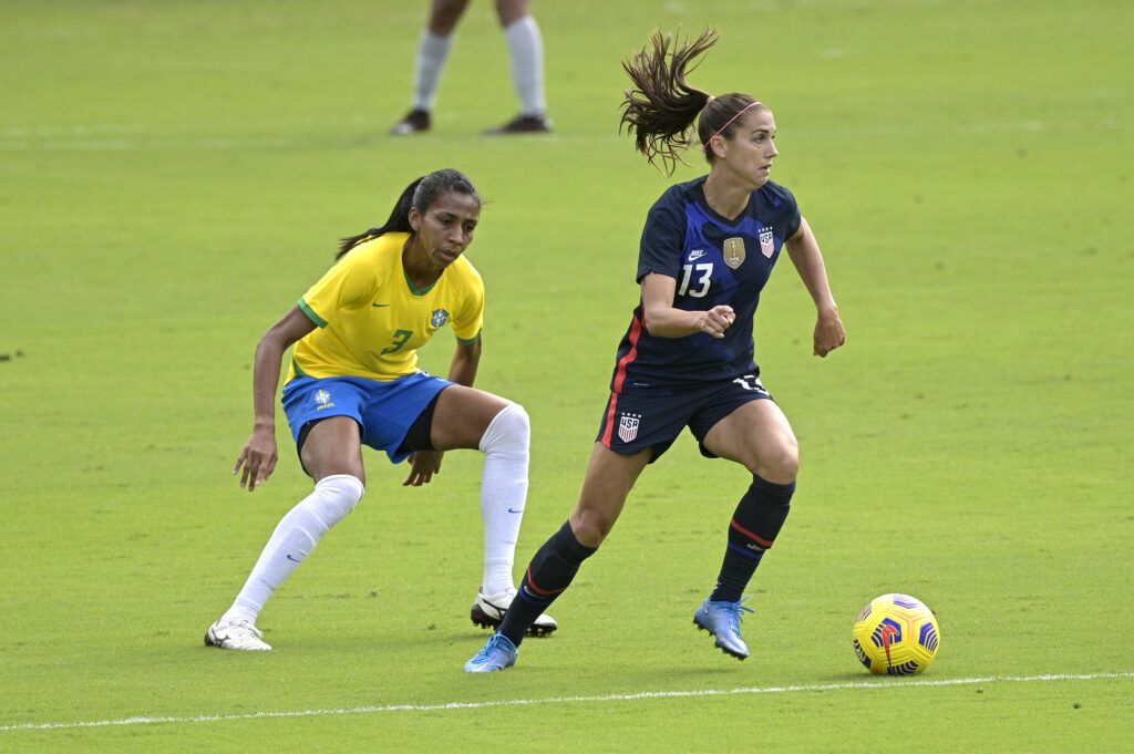 United States forward Alex Morgan (13) controls a ball in front of Brazil defender Bruna Benites (3) during the first half of a SheBelieves Cup women's soccer match, Sunday, Feb. 21, 2021, in Orlando, Fla.