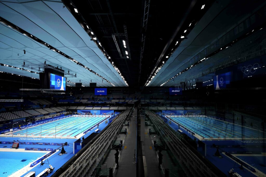The pool of the Tokyo Aquatics Centre is reflected in a window during a swimming training session at the 2020 Summer Olympics, Wednesday, July 21, 2021, in Tokyo, Japan.
