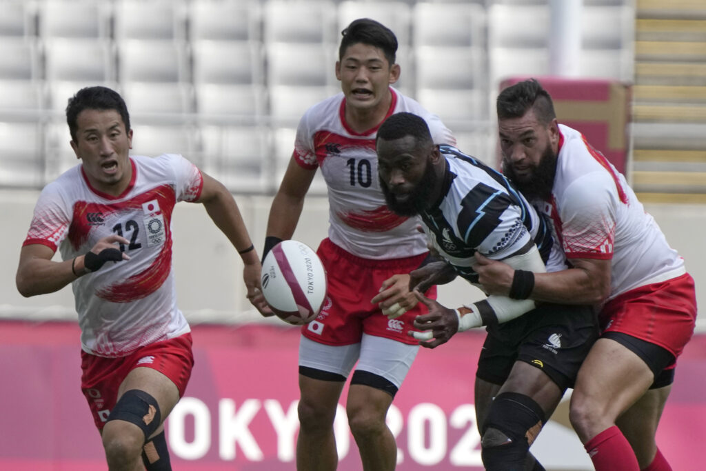 Fiji's Semi Radradra, second from right, and Japan's players, Naoki Motomura, left, Yoshikazu Fujita, second from left, and Colin Raijin Bourk, look on a loose ball during their men's rugby sevens match at the 2020 Summer Olympics, Monday, July 26, 2021, in Tokyo.