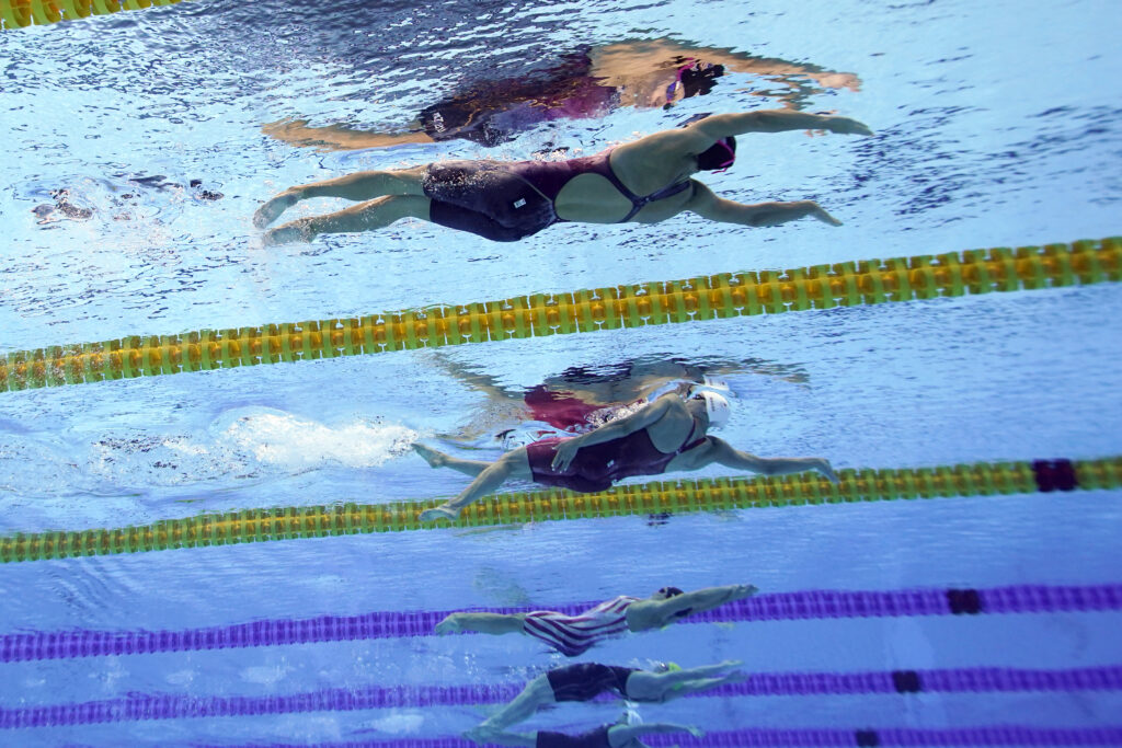 United States' Rhyan Elizabeth White, center in the striped suit, swims in the 100-meter backstroke final at the 2020 Summer Olympics, Tuesday, July 27, 2021, in Tokyo. United States' Regan Smith, top, won bronze, Canada's Kylie Masse, in the white cap, won silver.