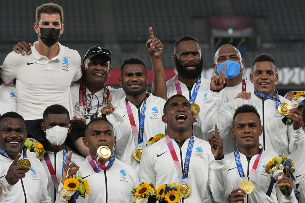 Fiji's players celebrate on the podium with their gold medals in men's rugby sevens at the 2020 Summer Olympics, Wednesday, July 28, 2021 in Tokyo, Japan. Semi Radradra is on the back row, third from the right.