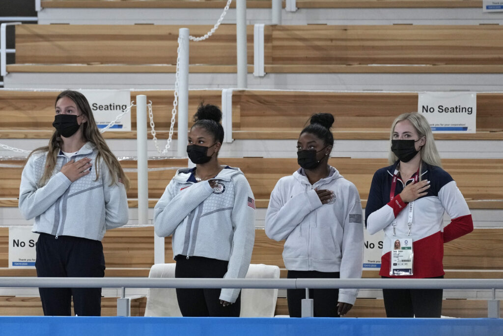From left, United States gymnast Grace McCallum, Jordan Chiles, Simone Biles and MyKayla Skinner stands for their national anthem as teammate Sunisa Lee receives the gold medal for the artistic gymnastics women's all-around at the 2020 Summer Olympics, Thursday, July 29, 2021, in Tokyo.
