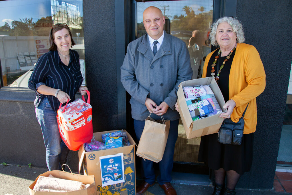 Foster Hope board chair Louise Burnie accepts donated items from Justin Neoiti and Yvonne Rameka from the Pacific Area Office in Auckland. New Zealand.