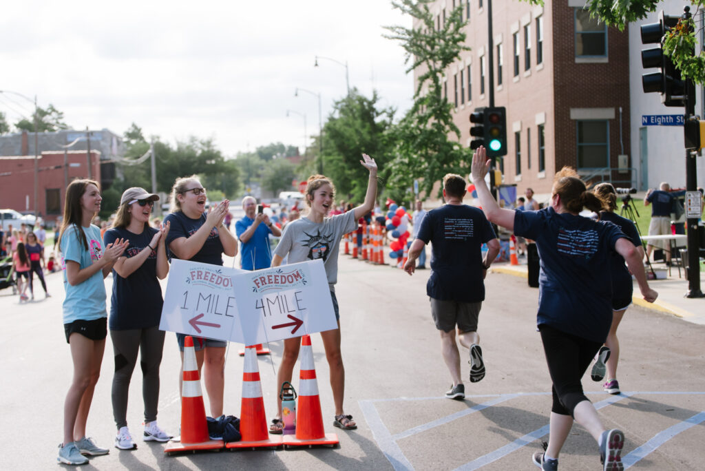 Runners are cheered on and congratulated as they cross the finish line of the 27th annual Parley P. Pratt Freedom Run held in Columbia, Missouri, on July 3, 2021.