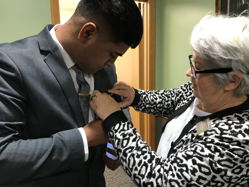 Sister Tina Dil, companion to New Zealand MTC President Lindsay Dil, helps an elder put on his missionary name tag for the first time on his arrival at the New Zealand Missionary Training Center in Auckland, New Zealand, on June 30, 2021.