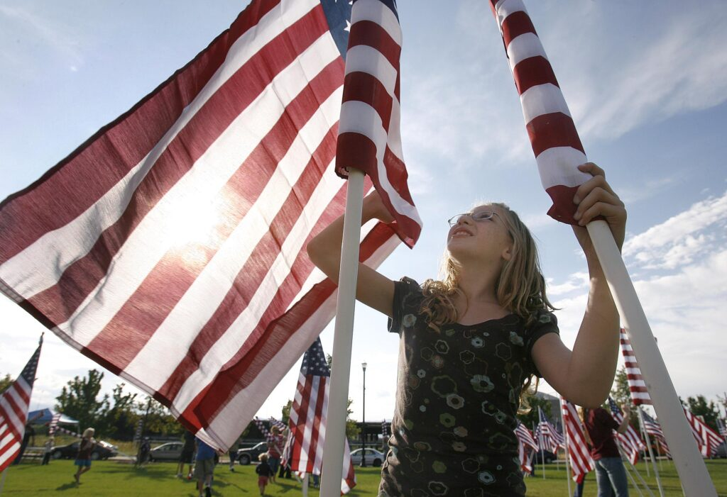 Amy McCaffree of Sandy unwinds an American flag as she helps many other volunteers to place 1776 flags near the Sandy City Hall to commemorate the 9/11 attacks. Sept. 10, 2008 Photo by Stuart Johnson