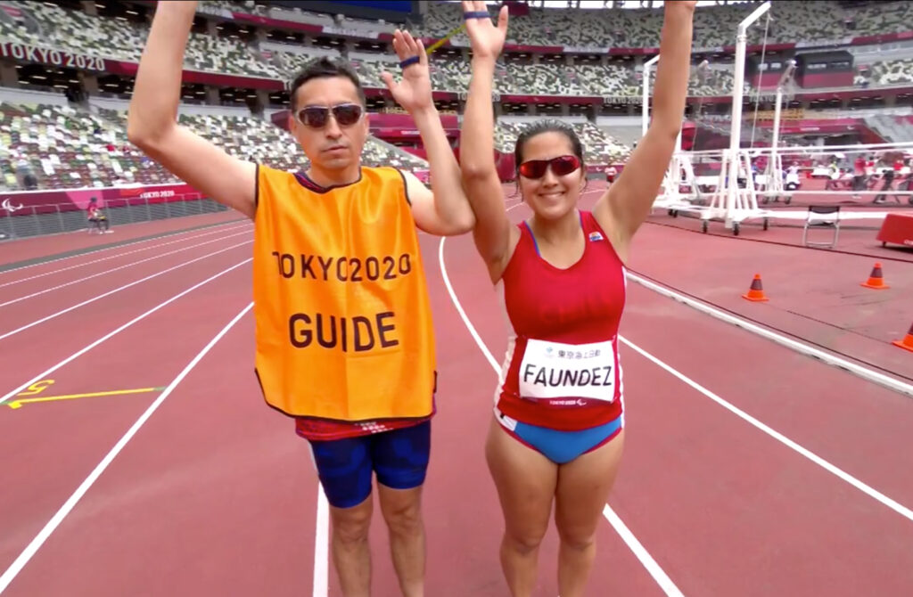 Margarita Faundez of Chile and guide Francisco Segovia wave prior to competing in the women's 1,500-meter T11 round 1 heat 1 at the Tokyo 2020 Paralympic Games in Tokyo Sunday, Aug. 29, 2021.