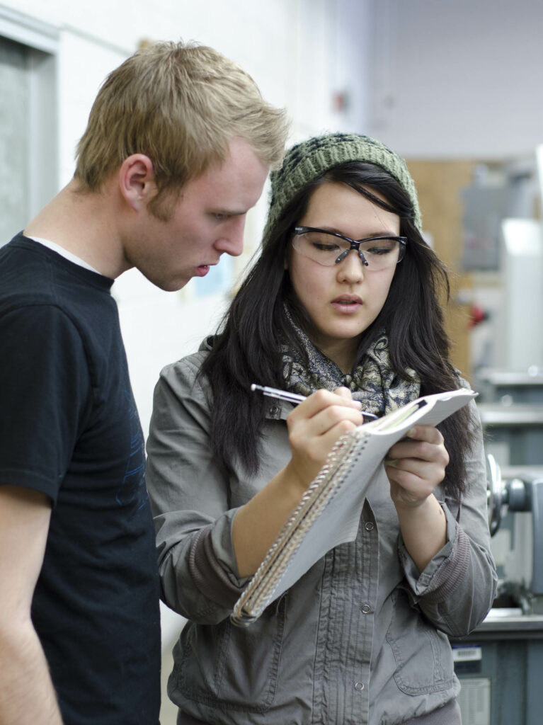 BYU-Idaho student Alyssa McCarter helps classmate Mike Cortez with a manufacturing processes lab assignment March 17, 2011. They are taking part in BYU-Idaho's schoolwide learning and teaching process of teaching each other.