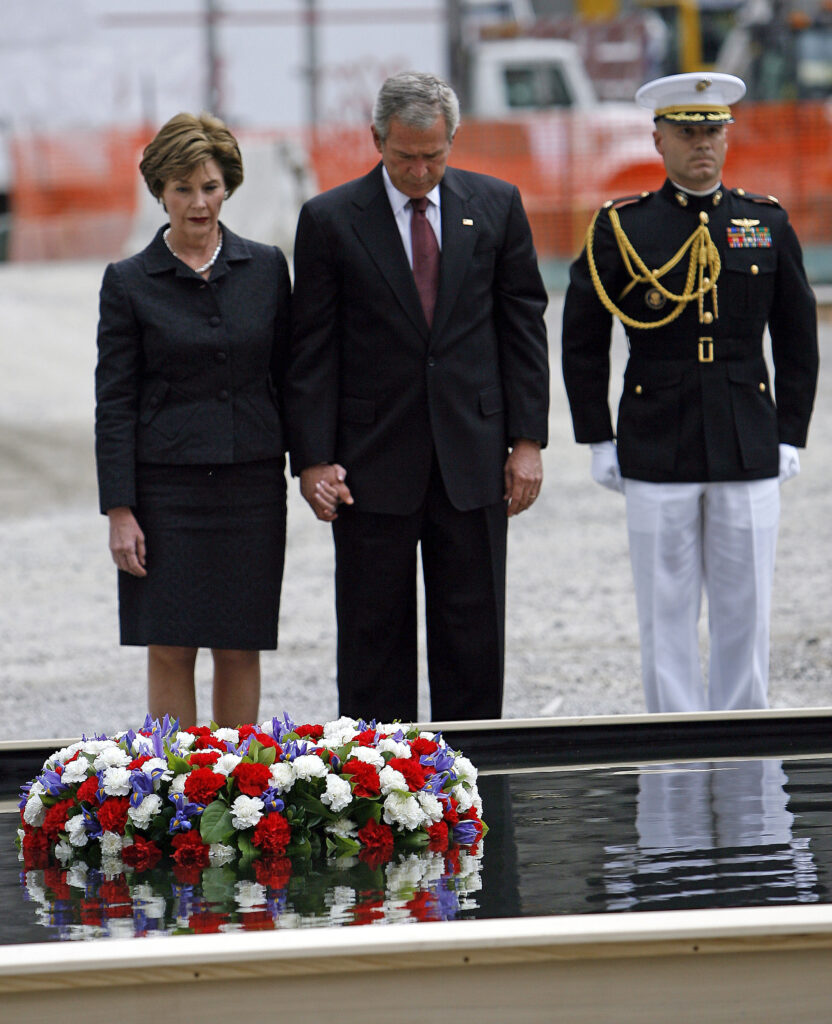 A military escort stands at attention as President Bush and first lady Laura Bush observe a moment of silence after laying a memorial wreath in a reflecting pool at ground zero Sunday, Sept 10, 2006. Bush was in New York to help commemorate the fifth anniversary of the Sept. 11, 2001 terrorist attacks. (AP Photo/Jason DeCrow)