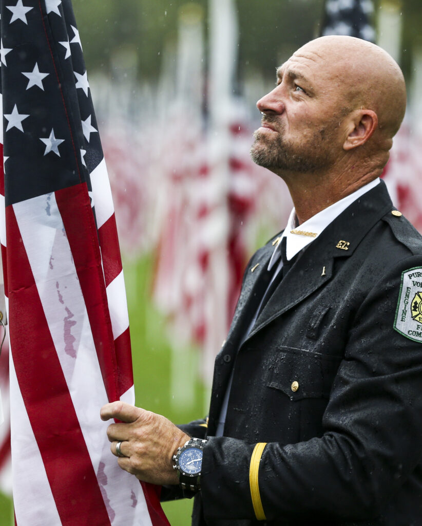 Phil Larsen, a retired firefighter with the Round Hill Volunteer Fire Department in Washington, D.C., braves the rain at the 18th annual Healing Field in Sandy on Wednesday, Sept. 11, 2019, as he pays his respects to the men and women who lost their lives during the 9/11 attacks.Larsen, a Sandy native, worked at the Pentagon in 2001 but was off the day of the attack.