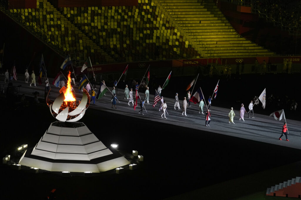 The Olympic flame burns as athletes and volunteers carry flags during the closing ceremony in the Olympic Stadium at the 2020 Summer Olympics, Sunday, Aug. 8, 2021, in Tokyo, Japan.