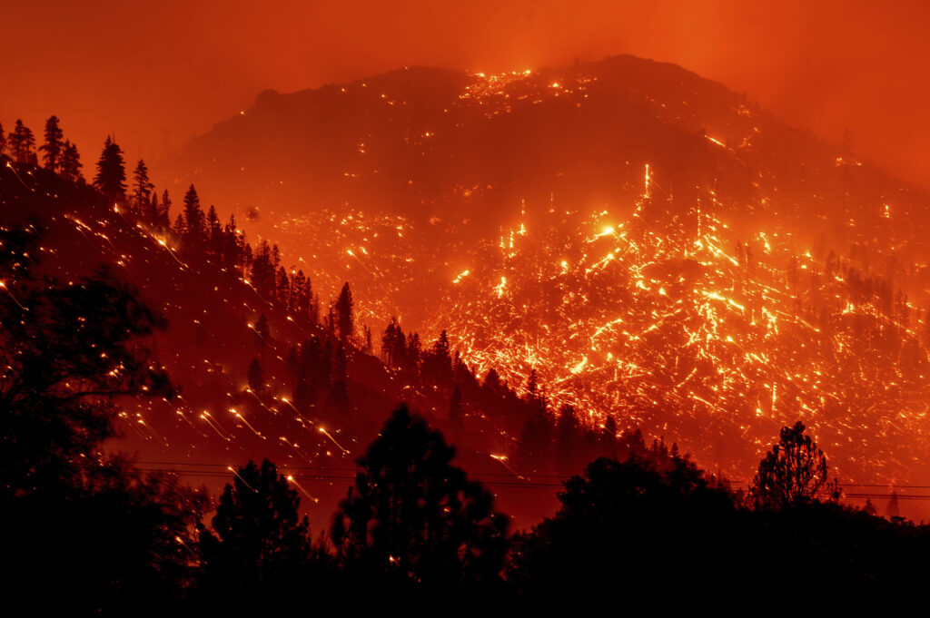 Seen in a long-exposure photograph, embers light up hillsides as the Dixie Fire burns near Milford in Lassen County, Calif., on Tuesday, Aug. 17, 2021.