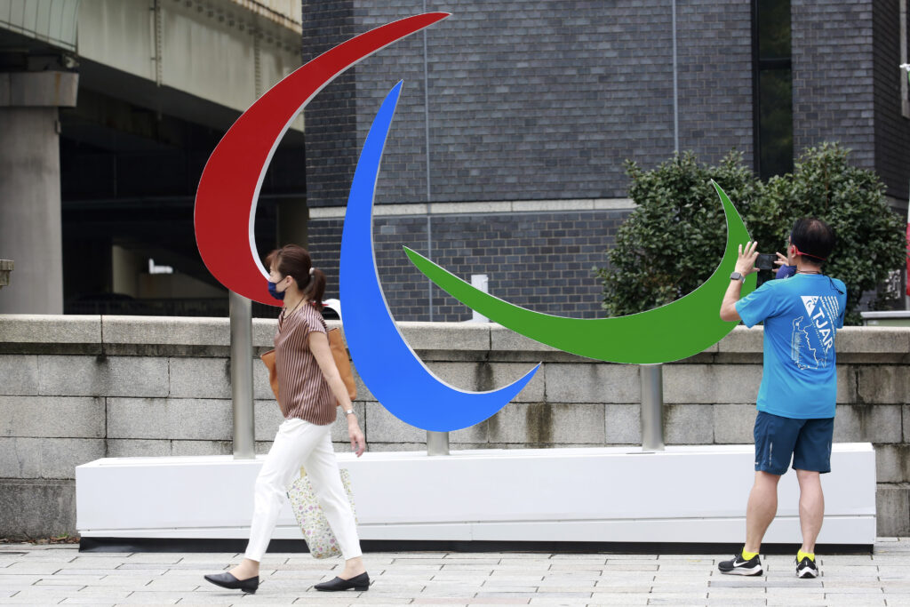 People walk by the Tokyo 2020 Paralympics symbol in Tokyo, Tuesday, Aug. 24, 2021.