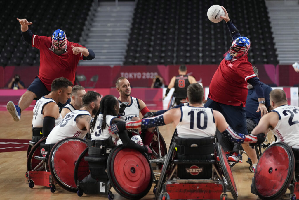 U.S. players celebrate with their staff wearing Stars and Stripes masks after their win over Canada at a wheelchair rugby pool phase group match at the Tokyo 2020 Paralympic Games, Thursday, Aug. 26, 2021, in Tokyo, Japan.